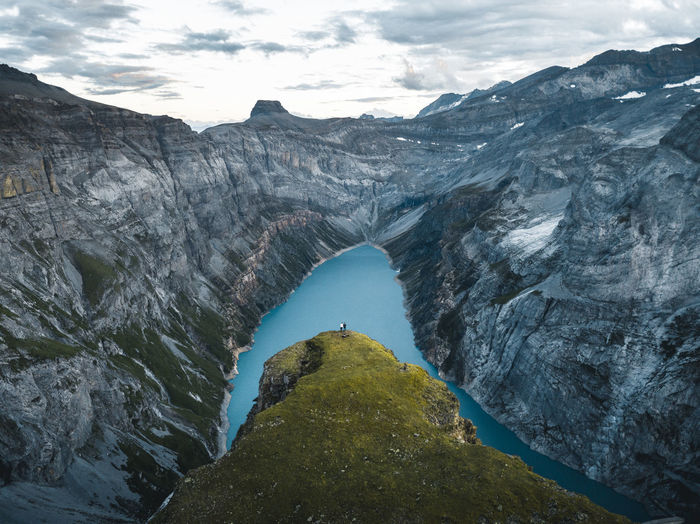 Two friends watching the sunset over the limmerensee near the muttseehütte in the swiss alps.