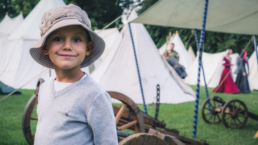 Portrait of boy wearing hat standing against tents