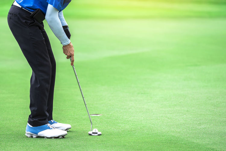 Low section of man playing golf on grassy field
