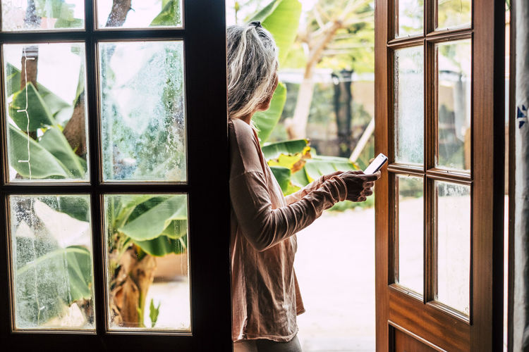 Side view of woman using phone while standing at entrance of home