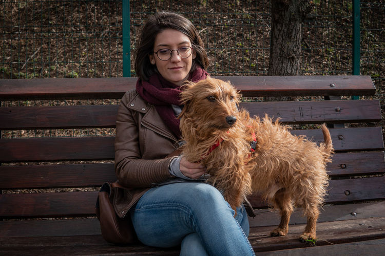 One Animal Mammal Pets Domestic Animals Sitting Domestic One Person Canine Dog Real People Outdoors Owner Park Spring Love Young Young Adult Happiness Happy Portrait Looking At Camera Women Casual Clothing Leisure Activity Bench Vertebrate Pet Owner