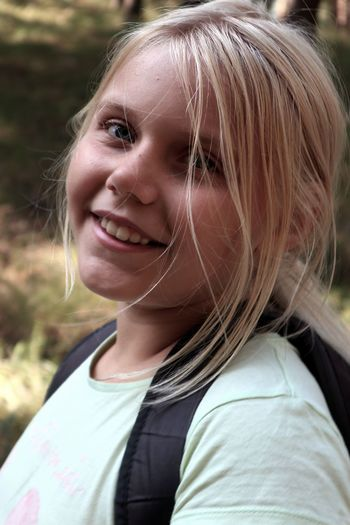 Close-up portrait of girl smiling while standing outdoors