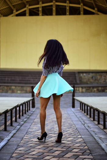 Rear view full length of young woman walking on footpath at amphitheater