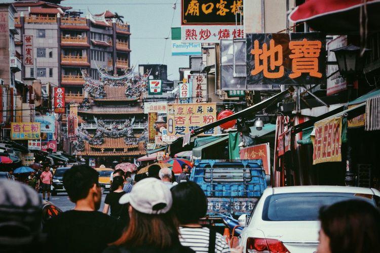 People in market against buildings