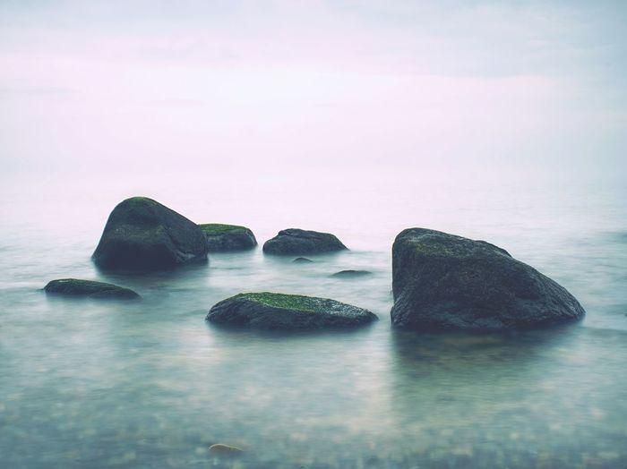 Rocks in sea, long exposure makes moody soft water level. melancholy blue mood