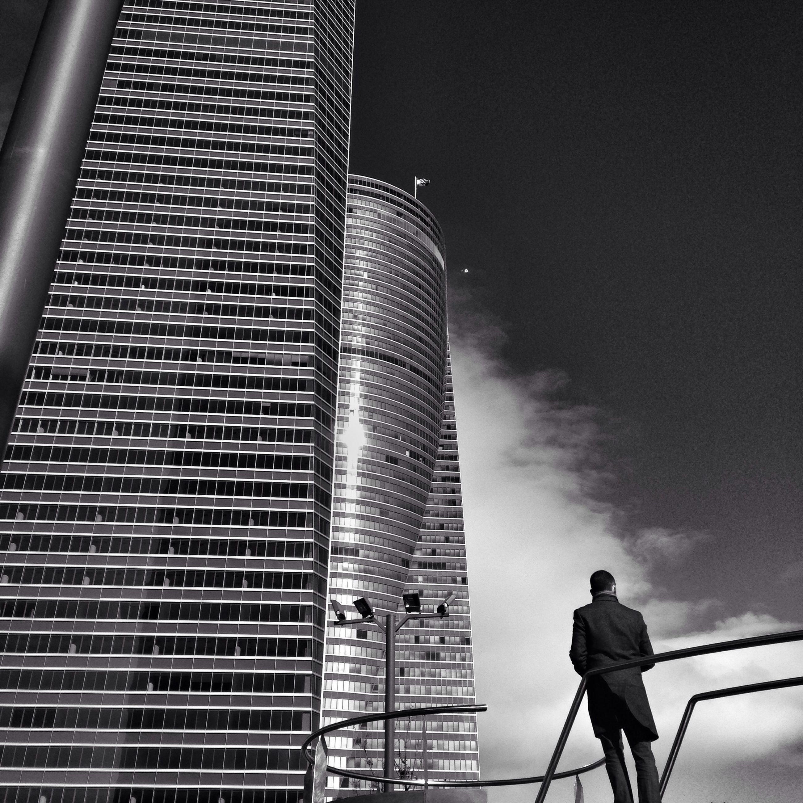 built structure, architecture, building exterior, low angle view, men, lifestyles, leisure activity, standing, city, rear view, sky, tower, tall - high, modern, casual clothing, building, city life, skyscraper