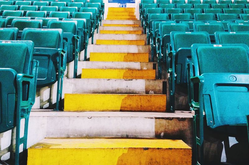 Steps amidst empty bleachers at stadium during sunny day