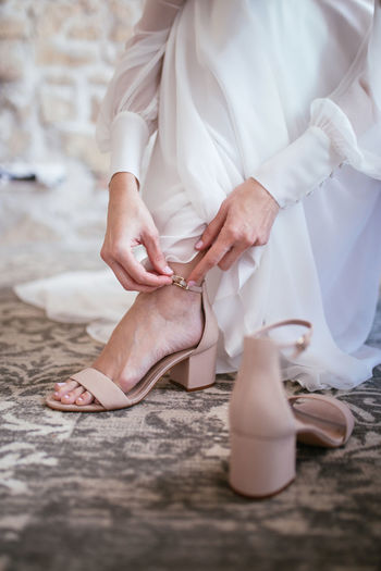 Closeup of a bride in white lace wedding dress put on her shoes. modern bridal style.
