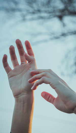 Close-up of hands against sky