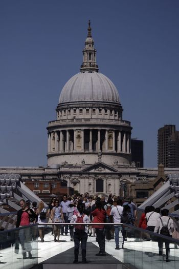 People on footbridge against st pauls cathedral