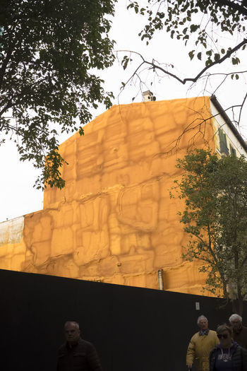 Rear view of people standing by building against sky