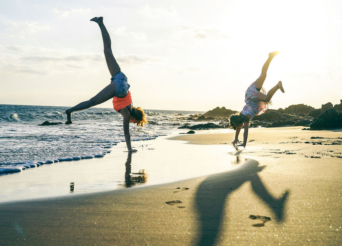 Happy mother and daughter Mother Daughter Family Beach Summer Love Child Mom Fun Vacations Real People Land Water Sea Lifestyles Nature Shadow Sand Sunlight People Human Arm Women Day Arms Raised Handstand