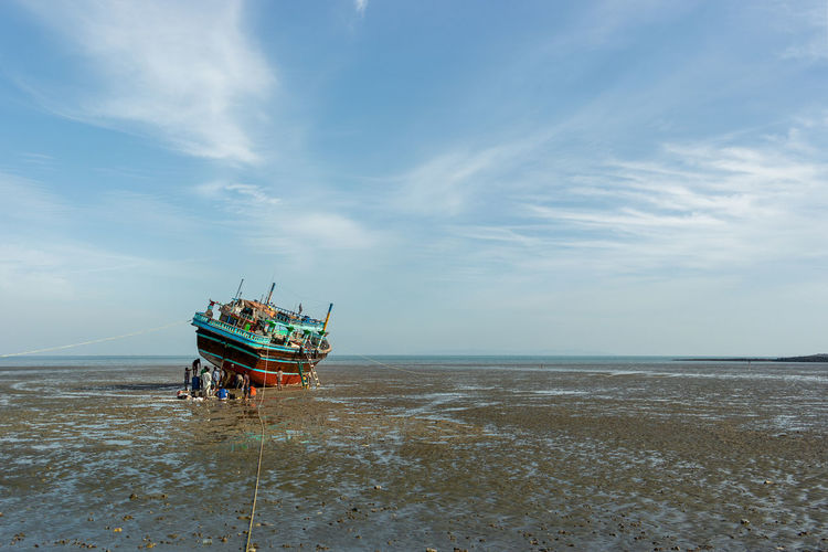 An old repurposed fishing boat is beached during low tide on a South Iran beach for repair. Repairing Beach Beauty In Nature Boat Cloud - Sky Day Horizon Horizon Over Water Land Low Tide Mode Of Transportation Motion Nature Nautical Vessel No People Outdoors Scenics - Nature Sea Sky Transportation Travel Water