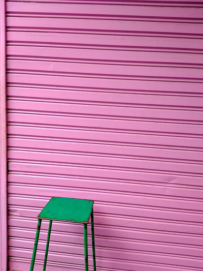 The green chair is in front of the pink wall. Minimal style. Pink Color Pattern No People Shutter Wall - Building Feature Corrugated Iron Full Frame Day Built Structure Architecture Iron Closed Multi Colored Metal Indoors  Striped Security Backgrounds Red Green Color Corrugated Minimalism