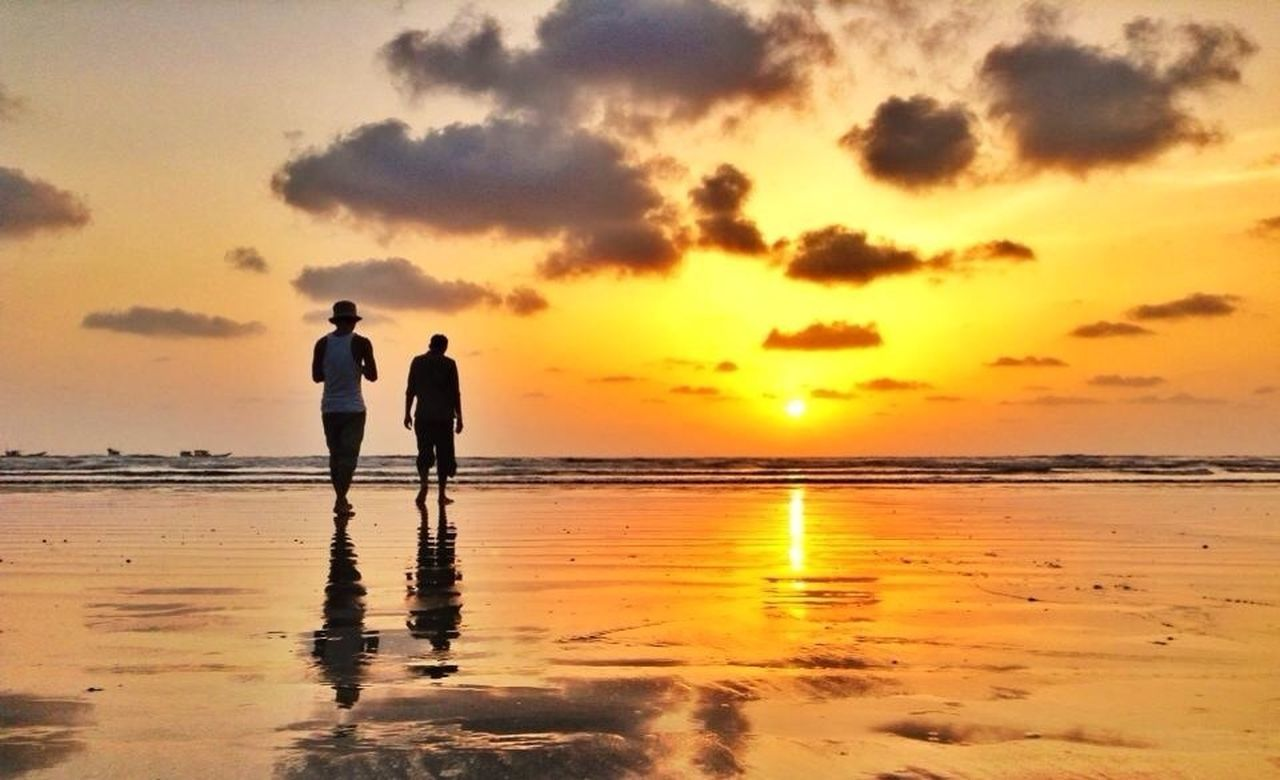 sea, sunset, beach, water, horizon over water, shore, sky, scenics, orange color, silhouette, beauty in nature, sand, reflection, tranquil scene, tranquility, leisure activity, standing, idyllic, sun