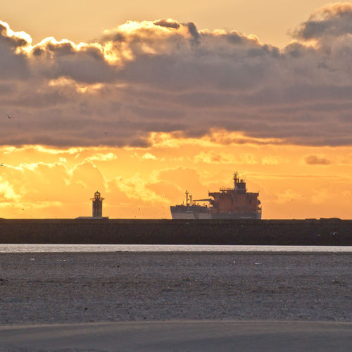 Approaching Harbour Lighthouse Tanker Beach Activities Beachphotography Cloud - Sky Nature No People Orange Color Outdoors Seascape Sky Sunset Tanker Ship Water