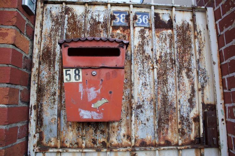 Close-Up Of Old Mailbox On Rusty Door