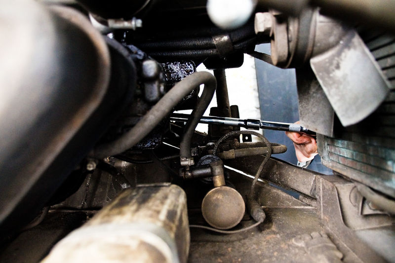 Close-up of mechanic working on car engine