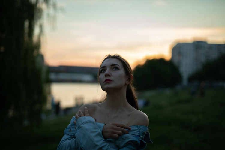 Young woman looking away while standing outdoors during sunset