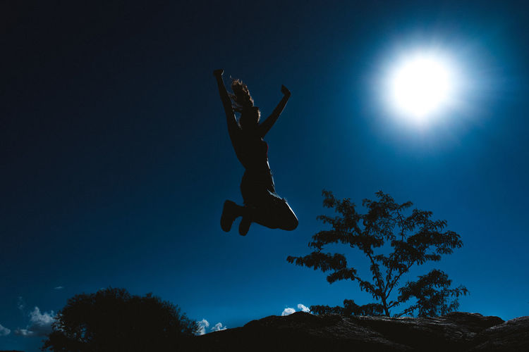 Humanity Meets Technology Sky Mid-air Low Angle View Jumping Nature Human Arm Silhouette One Person Blue Full Length Tree Plant Arms Raised Real People Sport Leisure Activity Lifestyles Outdoors Night Excitement International Women's Day 2019