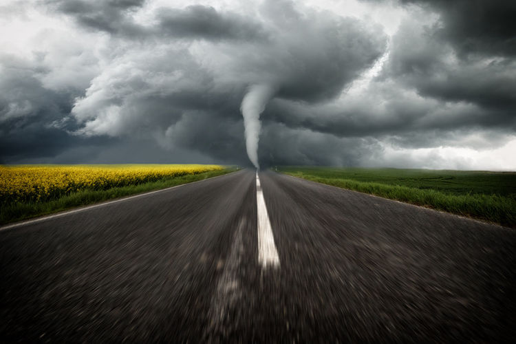 Road passing through field against storm clouds