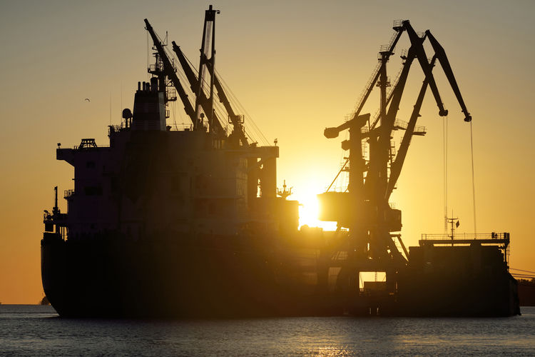 Silhouette of commercial dock against sky during sunset