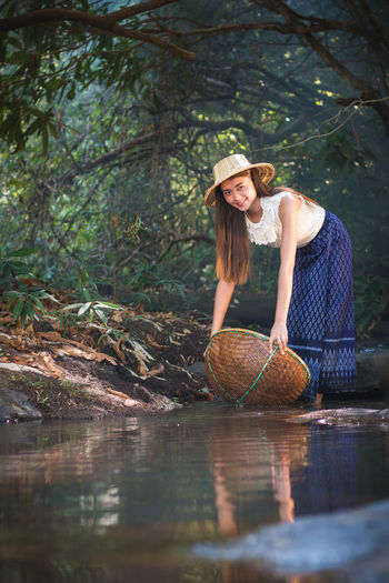 Portrait of smiling young woman holding basket while standing by lake in forest
