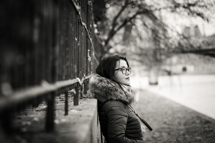 Side view of young woman standing by retaining wall during winter