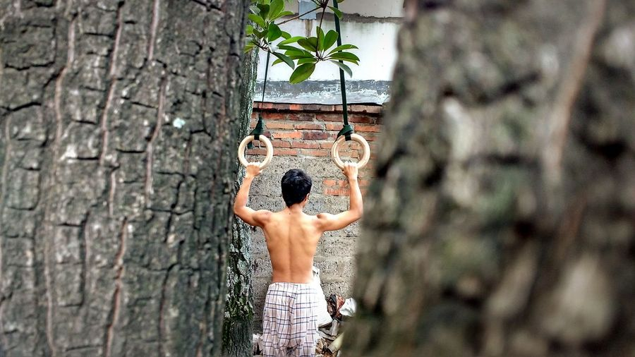 Rear View Of Shirtless Man Holding Gymnastic Rings
