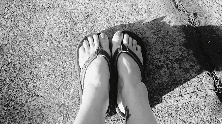 Low section of woman wearing flip-flops on footpath