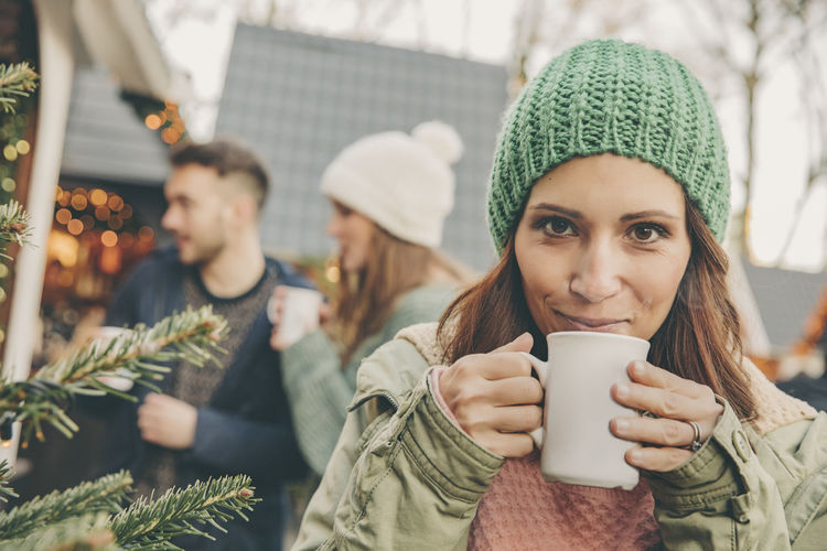 Portrait of young woman drinking coffee in winter