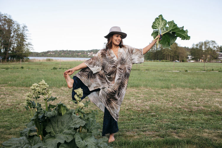 Full length portrait of young woman standing in farm