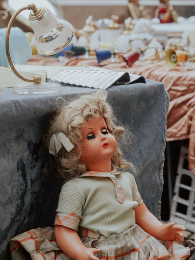 Doll by table for sale in shop