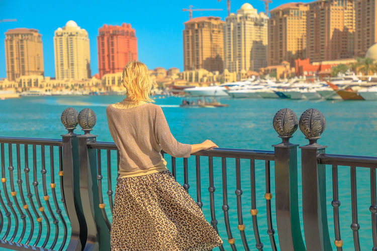 Tourism in Qatar. Blonde elegant woman at Marina walkway looks at Porto Arabia, The Pearl-Qatar's main harbor. Carefree tourist with open arms in Doha, Persian Gulf, Middle East in Arabian Peninsula. Doha Doha,Qatar Qatar City Town Waterfront Sea Skyline Woman Model Girl Female Tourist Seascape Tourist Attraction  The Pearl, Doha The Pearl Cityscape Holiday Vacation People Architecture Water Railing Built Structure Building Exterior Women One Person Real People Adult Nature Sky Rear View Day Leisure Activity Lifestyles Hair Looking At View Outdoors Hairstyle Office Building Exterior Skyscraper