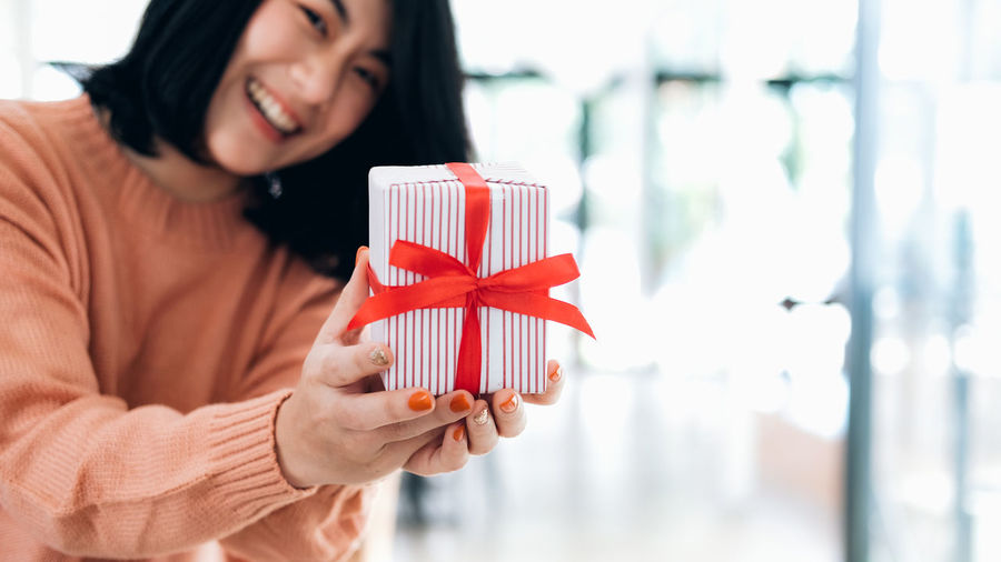 Portrait of smiling young woman holding gift box