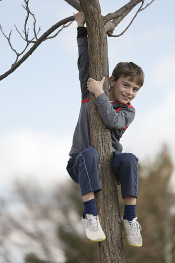 10-year-old boy climbing on a tree looking towards the camera. Horizontal shot with natural light Boys Childhood Day Focus On Foreground Full Length Leisure Activity Lifestyles Nature One Person Outdoors People Sky Tree