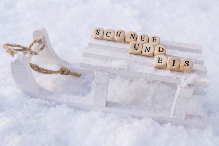 Close-up of text with toy blocks on sled over snow covered field