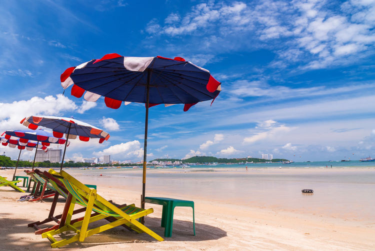 Deck chairs and parasols on shore at beach against sky