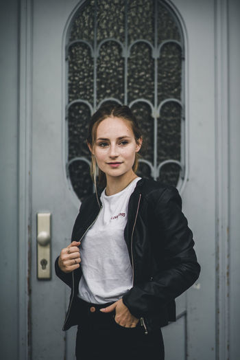 Young Woman Wearing Leather Jacket While Standing By Door