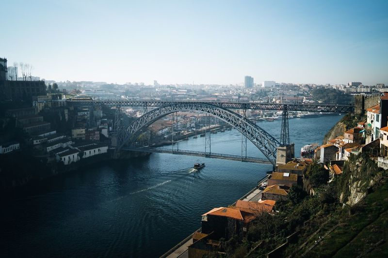Porto Bridge with a boat crossing the river EyeEm Selects Architecture Built Structure Building Exterior City Sky Water Cityscape Nature Building Clear Sky Bridge High Angle View River No People Bridge - Man Made Structure Transportation Day Outdoors