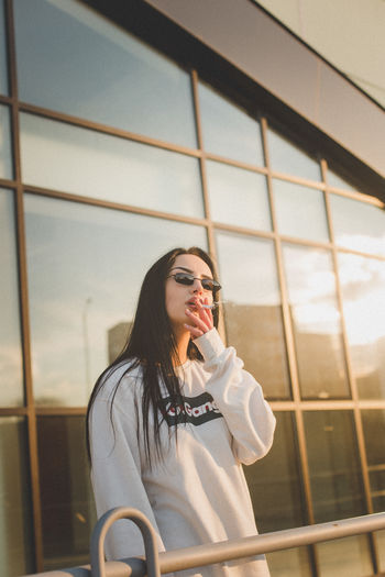 Portrait of young woman wearing sunglasses smoking cigarette standing in balcony during sunset