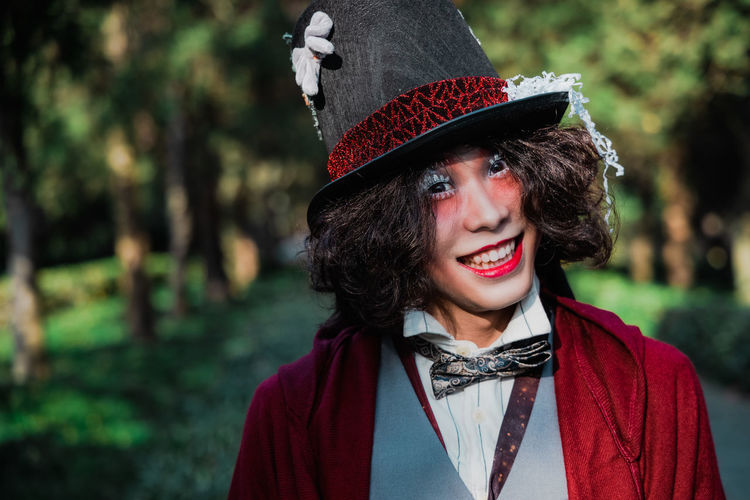 Portrait of a smiling young man cosplaying mad hatter
