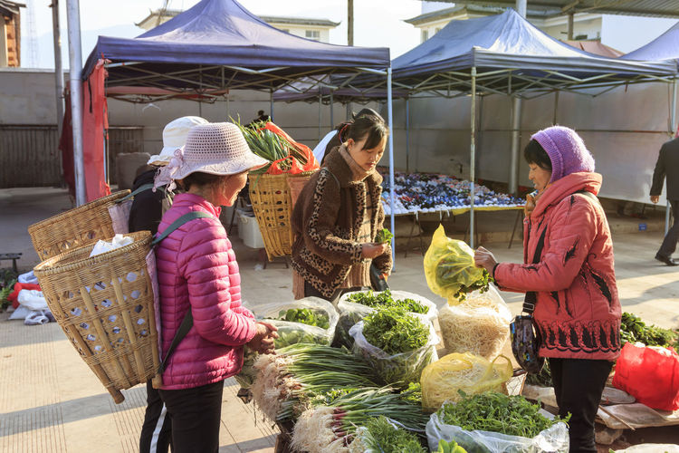 Shaxi, China - February 22, 2019: Chinese women selling local vegetables in the Friday market in Shaxi old town Shaxi China ASIA Yunnan Yunnan ,China Market South Silk Road Tea Horse Road Minority Ethnic Group Old Town Kunming, China Landscape People Night Teather Old