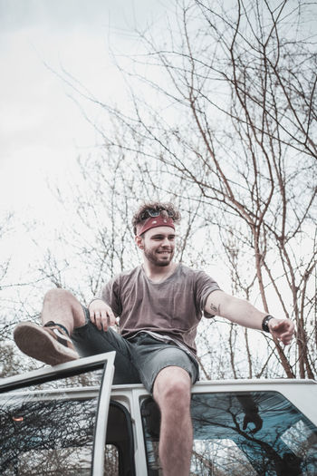 Low angle view of young man sitting on car roof