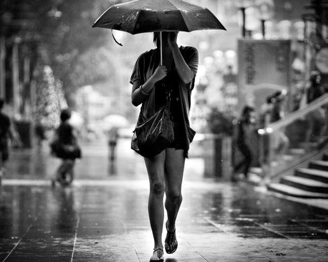 Woman With Umbrella Walking On Street During Rainy Season