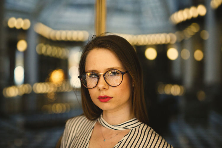 Portrait Of Young Woman Wearing Eyeglasses Against Illuminated Lights
