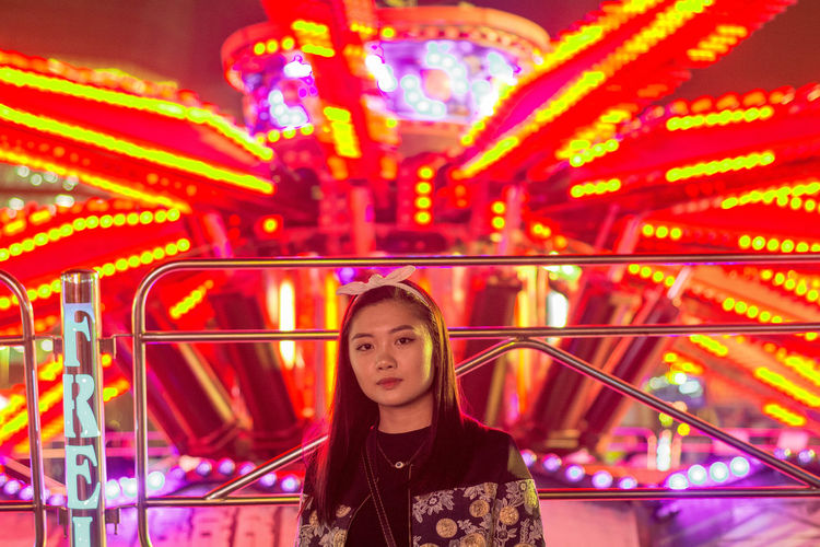 Portrait of young woman in amusement park ride at night