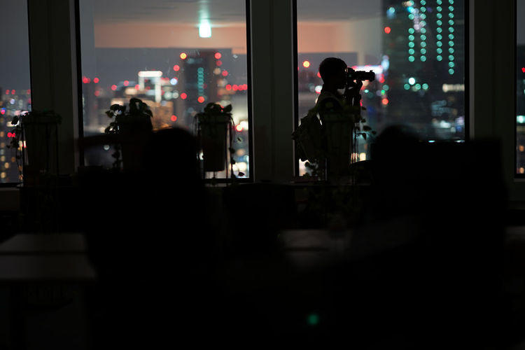 Silhouette people photographing illuminated at home