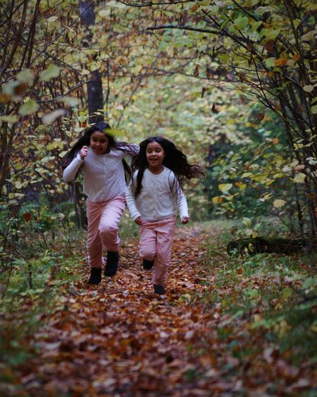 Full Length Of Playful Sisters Running In Forest During Autumn