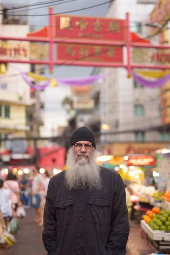 Portrait of man standing in city